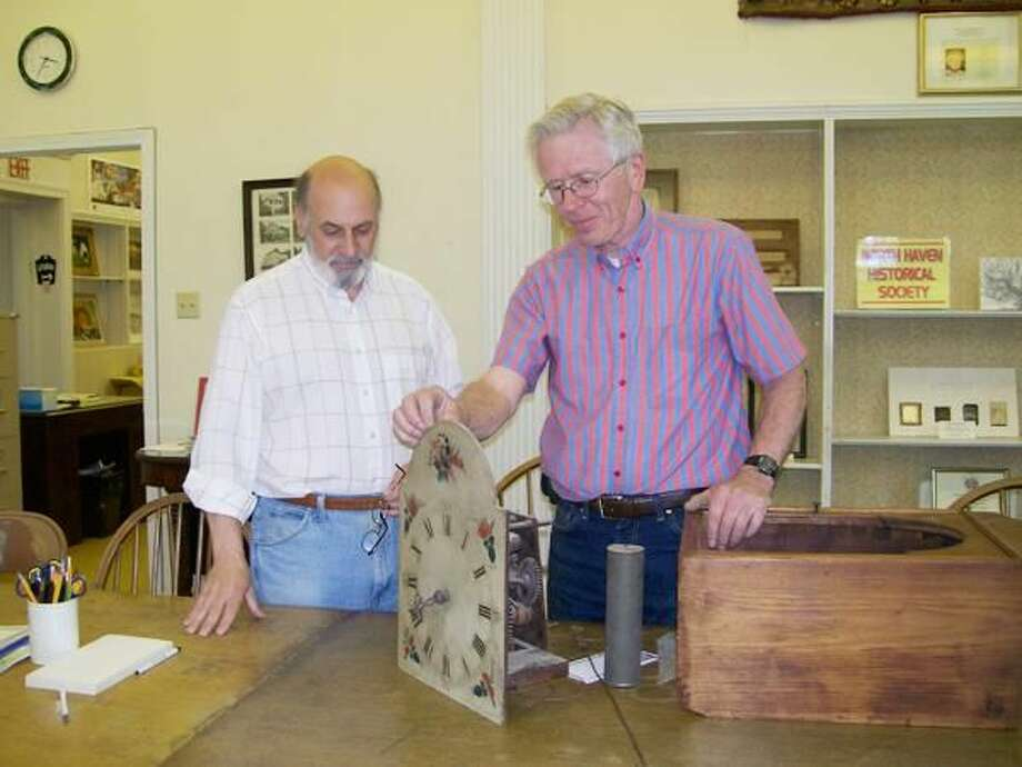 Submitted Photo North Haven Historical Society assistant curator Nick D'Errico and society treasurer Walt Brockett inspect the intricate wooden workings of an antique clock recently donated to the society by members of the Squires family. Society officials believe the clock, which dates back to the early 1800s, was made locally.
