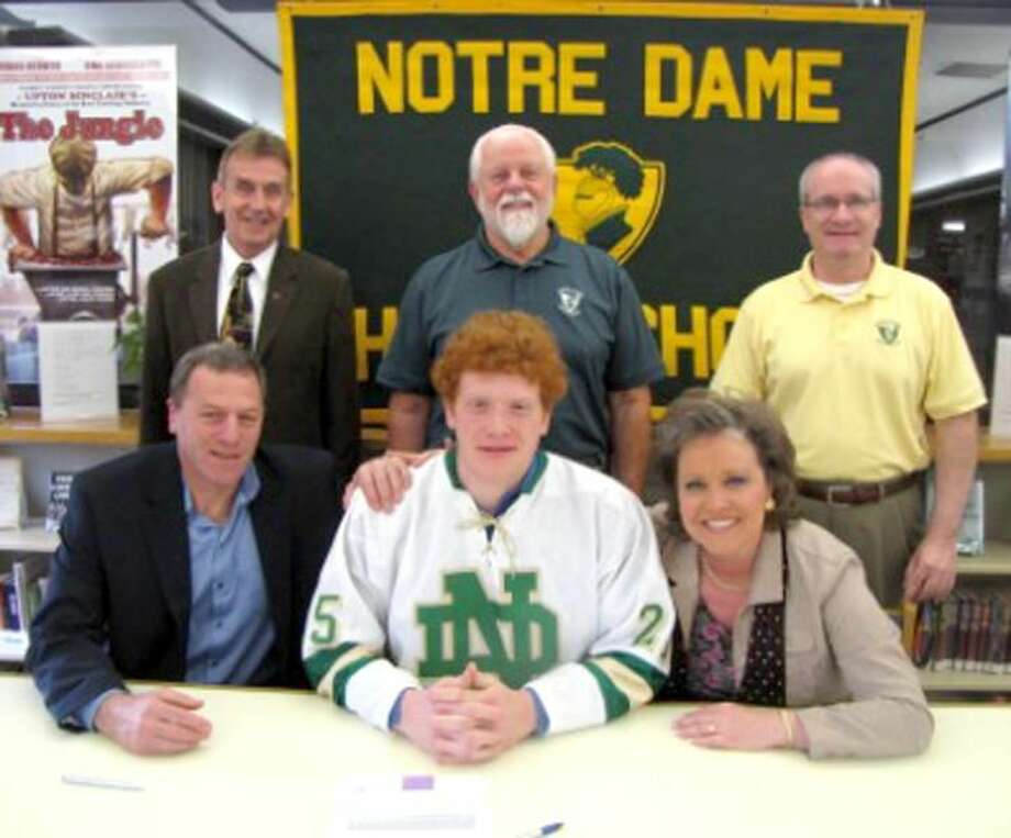 Luke Curadi signs his letter of intent to play Division I hockey at RPI. Curadi is flanked by his parents Richard and Denise. Watching from behind are Notre Dame President Br. James Branigan, C.S.C., hockey coach Bill Gerosa and Principal Patrick Clifford. (Submitted photo)