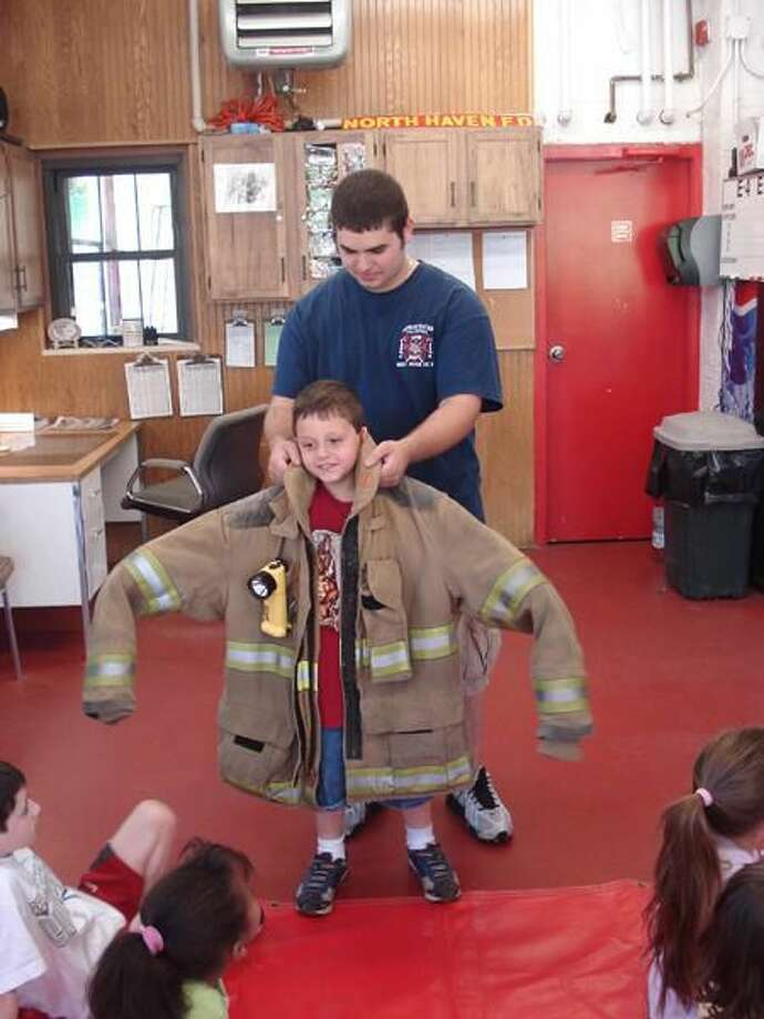 Submitted photo The Kindergarten students and the Transitional room from Ridge Road Elementary School visited the Ridge Road Firehouse on May 4. Pictured is Nicholas Giangrande trying on fireman gear.
