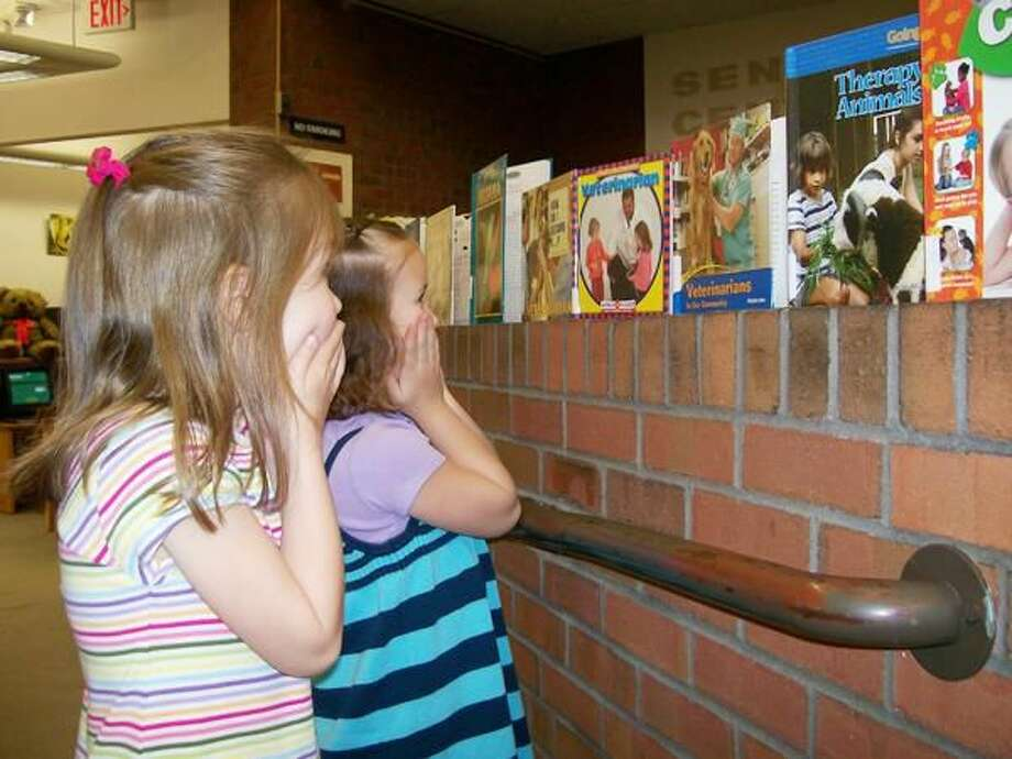 Photo by Lynn Fredricksen Kelsey Taylor (right) and Claire Flanagan (left), both kindergarten pupils at Spring Glen Elementary School, took great delight in the library's display for National Pet Week.