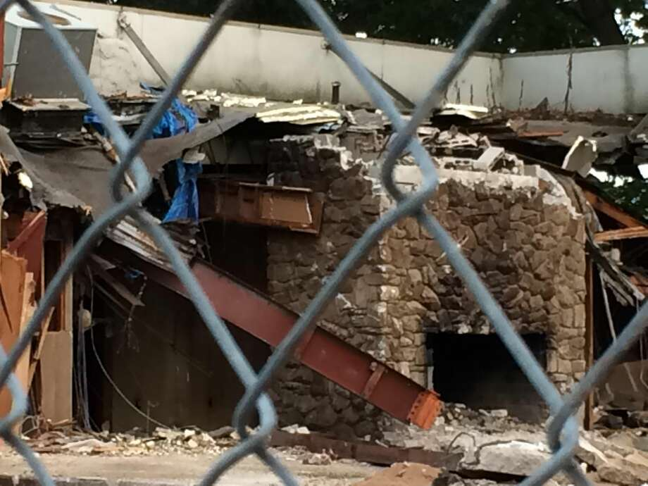 Photo by Lynn Fredricksen Demolition crews were on the scene last week as the building that held the iconic Rustic Oak restaurant was razed. Here, the remains of the fireplace are still visible mid-demolition.