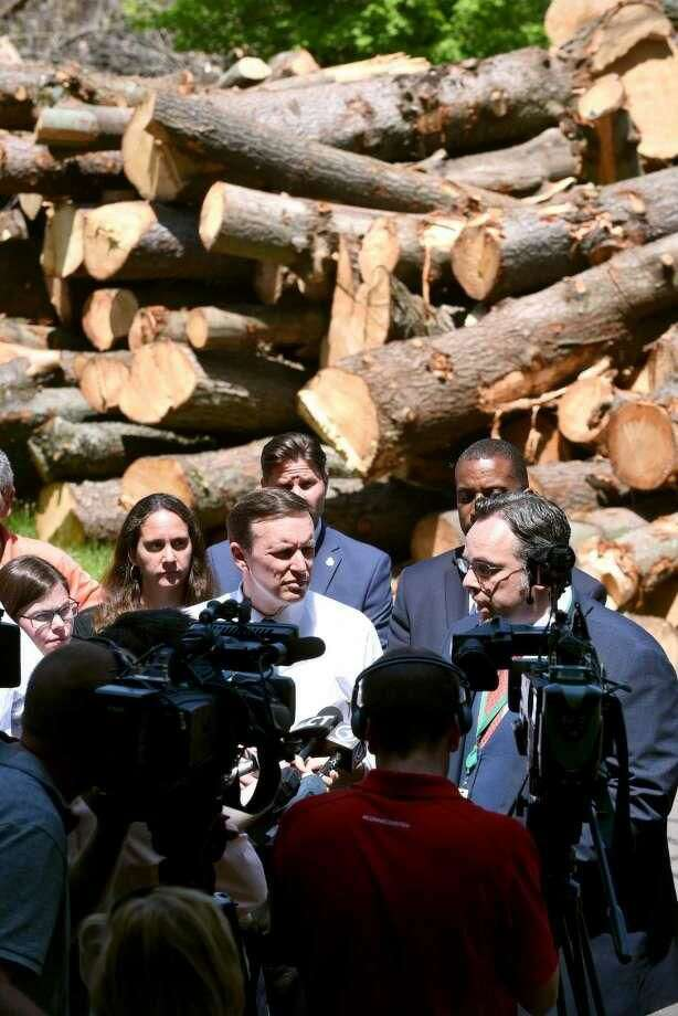 During a tour of storm damage in Hamden, U.S. Sen. Chris Murphy, center, listens to Hamden Mayor Curt Leng, right, speak with the media concerning storm damage in town, in a parking lot donated by Quinnipiac University for storm debris on Whitney Avenue.
