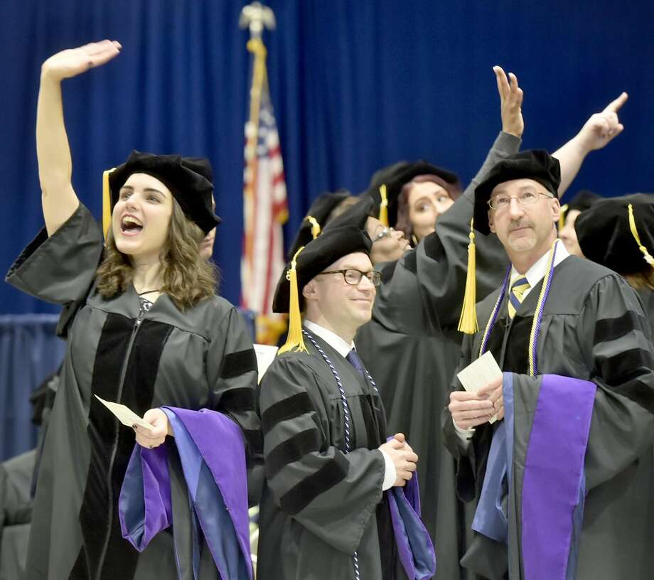 A graduate waves to the crowd during the pomp and circumstance of the processional during the 2018 Quinnipiac University School of Law Commencement and Doctoral Hooding exercises Sunday, May 13.