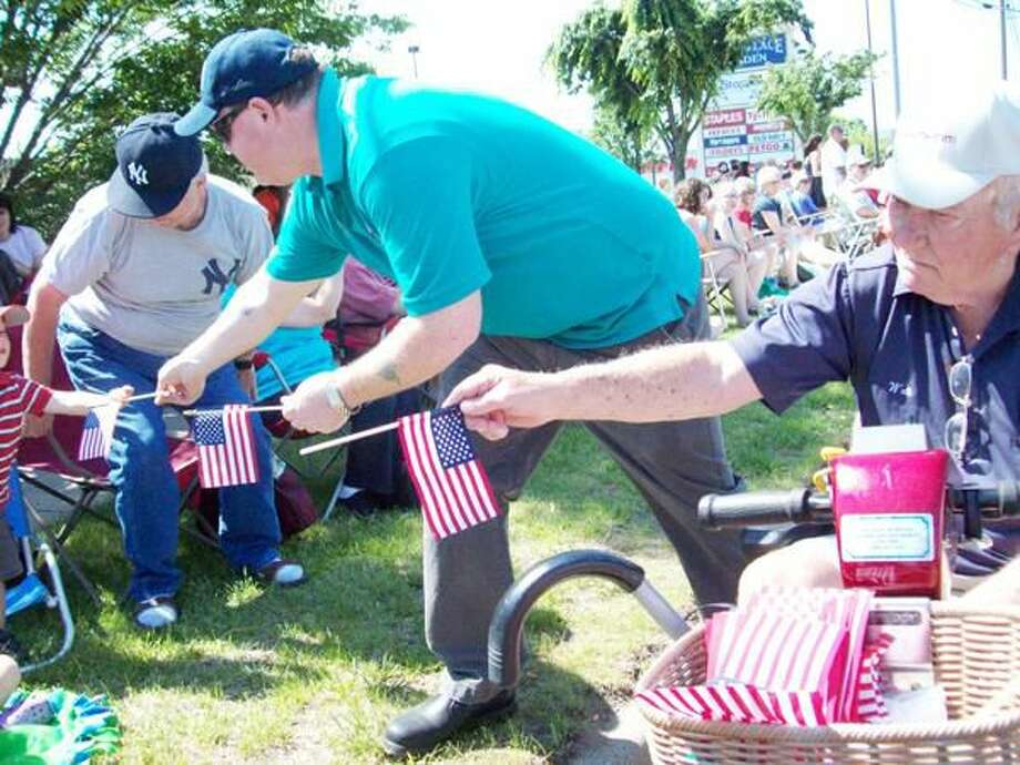 Submitted Photo Hamden ElksPresident Tim Mayer, left, with Veteran and Lodge member Walt Gannon hand out American flags along the Hamden Memorial Day Parade route. Members of Hamden Elks Lodge #2224, serving Hamden and North Haven, recently participated in both Hamden and North Haven Memorial Day Parades. Hamden Lodge members handed out approximately 3,000 American flags to spectators along the parade routes. The Elks will be hosting Flag Day ceremonies in North Haven on June 13 and in Hamden on June 14.