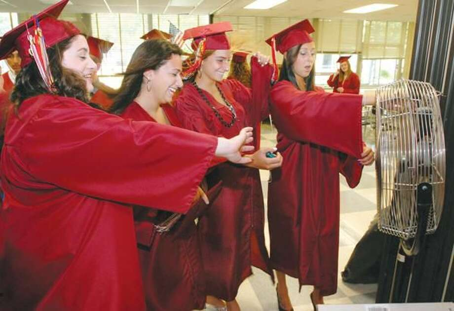 Photo by Mara Lavitt North Haven High School graduates left to right Caitlin Bracale, Susan Gambardella, Maria Sanzari and Tori Burr keep cool by a fan while waiting to line up for commencement.