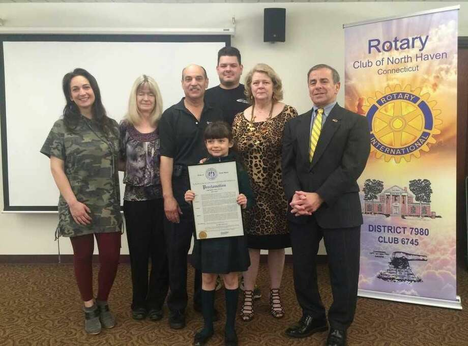 John Henry Graef Jr.'s family, from left: Stephanie Laudano, Cheryl Laudano, Frank Laudano, Braelyn Heusser (front), Chris Russo (back) and Susan Pace, at the North Haven Library with First Selectman Michael Freda.