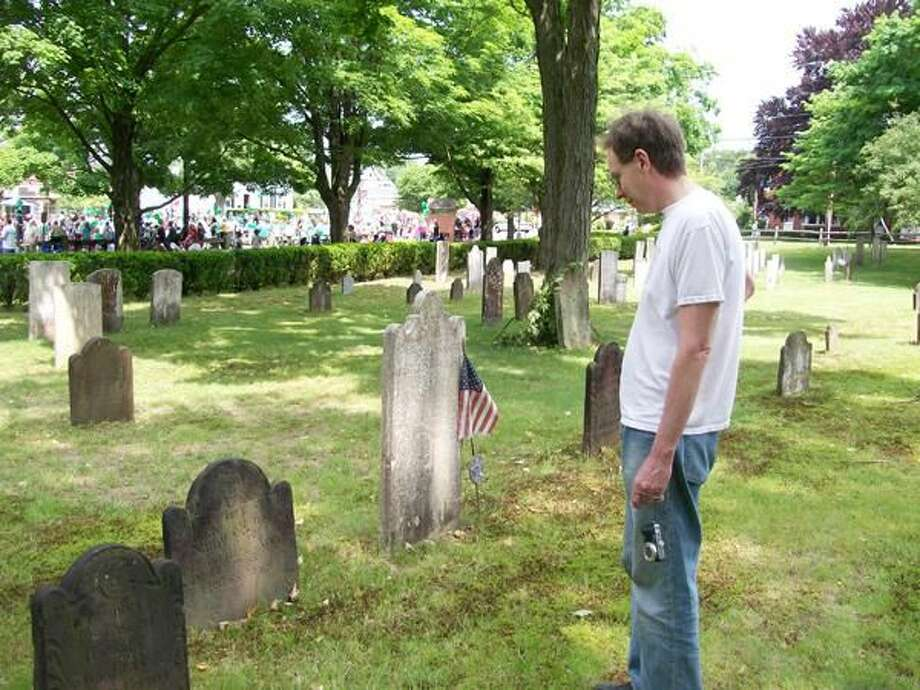 Photo by Lynn Fredricksen Woody Johnson, of Wallingford, PA, pauses to pay his respects in the Ancient Cemetery in North Haven as the North Haven Memorial Day Parade marches by in the background. Johnson was visiting town to see his nephew, Owen Evans, march in the parade with the North Haven High School Band. To see more Memorial Day photos from North Haven, Wallingford and Hamden, visit www.ctpostchronicle.com.