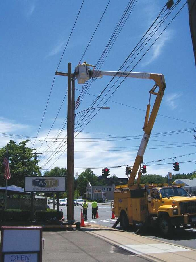 Photo by Lynn Fredricksen Crews from the United Illuminating Company work on relocating pole #2256 at the intersection of Skiff Street and Whitney Avenue.
