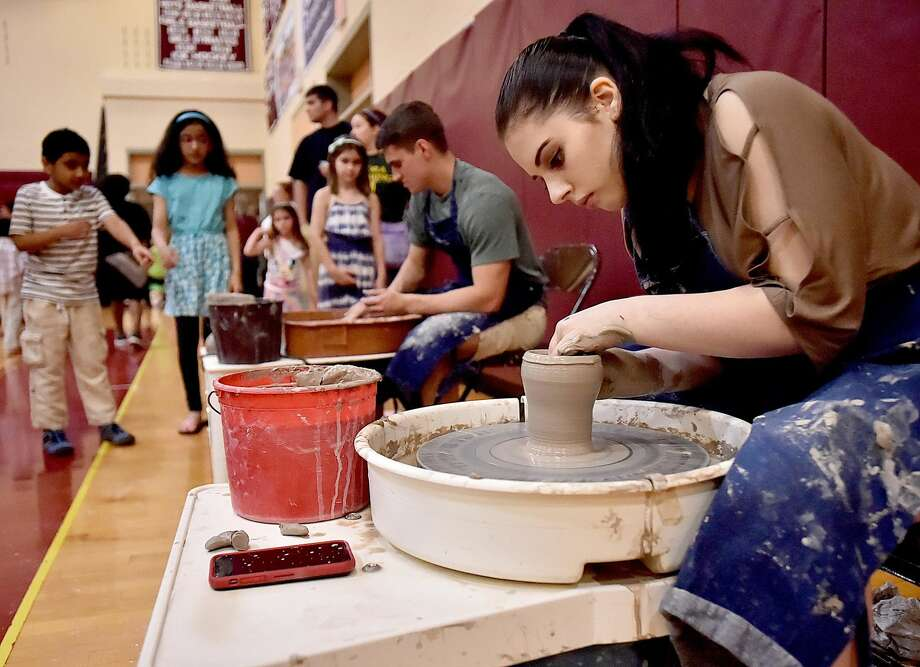 Sierra Kusmit, a senior in the ceramic design class and Jacke Bencivengo, a senior art student make bowls using pottery wheels at Art Beat at the North Haven Public Schools Art Celebration, Thursday, May 3 at North Haven High School.