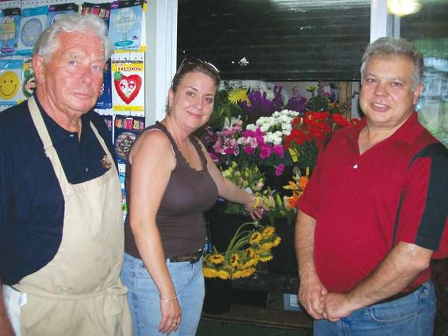 Photo by Lynn Fredricksen Gerry Pfeiffer, left, and Karen Morgan with Forget Me Not owner Luigi Nuzzolillo at the cooler containing numerous varieties of colorful flowers.