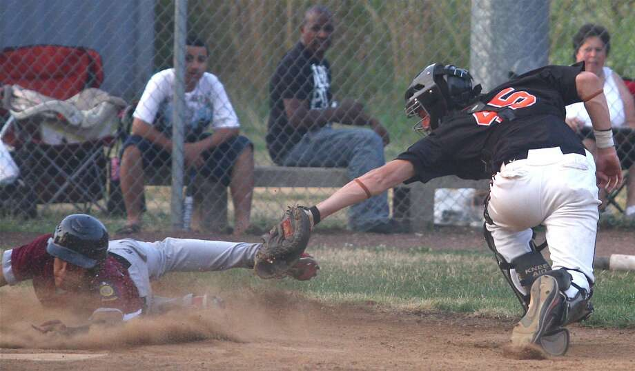 Photo by Russ McCreven North Haven's Edison Rodriguez tries to slide around Orange catcher Ryan Adams but is called out at the plate in Post 76's 3-2 win last Wednesday night at Brinley Field in Orange.