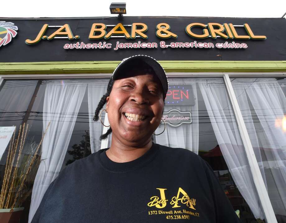 Theda Wray, co-owner of J.A. Bar & Grill, in front of the restaurant at 1372 Dixwell Ave. in Hamden.