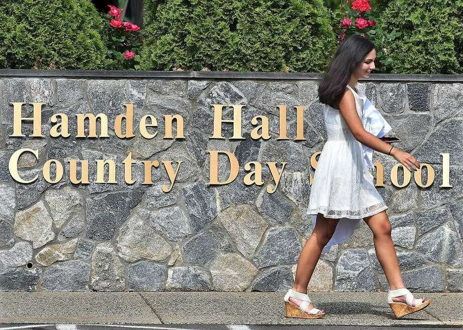 Sophia Lawder-Gill of New Haven carries her cap and gown on her way to the Taylor Performing Arts Center for commencement exercises at Hamden Hall Country Day School.