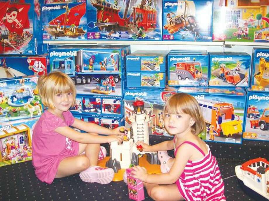 Photo by Lynn Fredricksen Children are always welcome to touch the merchandise at Evan's Toy Shoppe. Here, sisters Addison, 4 (left), and Peyton, 2 (right), busy themselves with a Playmobil set on a recent morning. The girls, who are visiting from New Jersey, were shopping with their grandmother, Marsha Moses of Hamden.