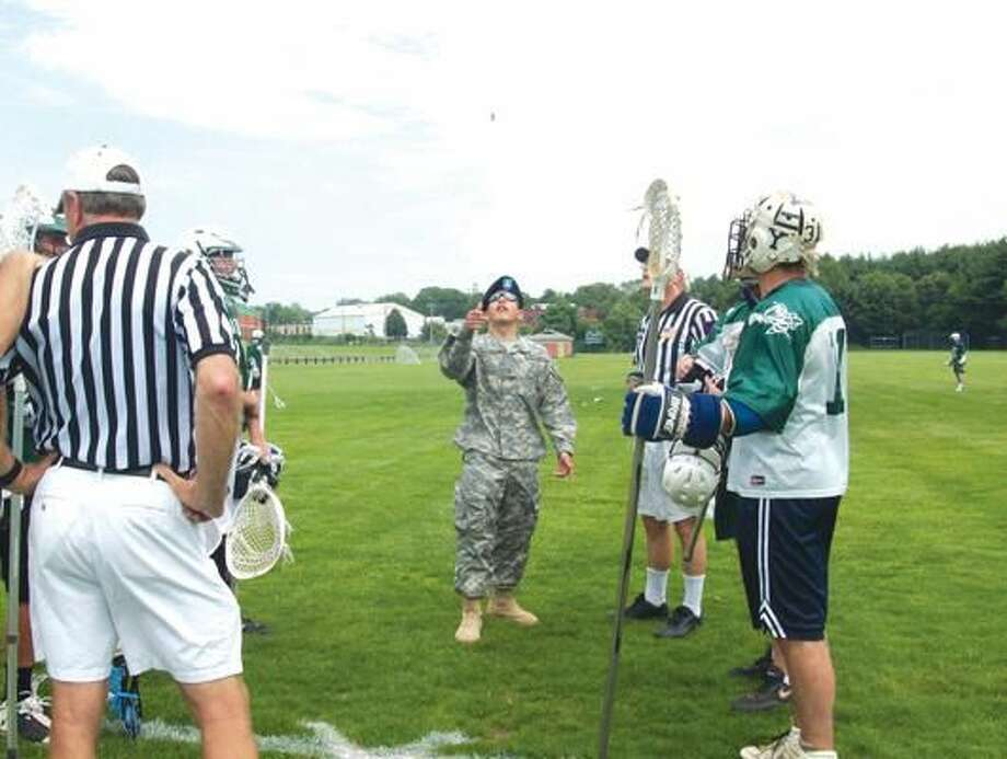 Submitted Photo Andrew Muolo, a Hamden soldier from the 101st Airborne Army Unit, serving in Afghanistan, flips the coin prior to Hamden Hall Country Day School Boys' Lacrosse annual varsity/alumni game.