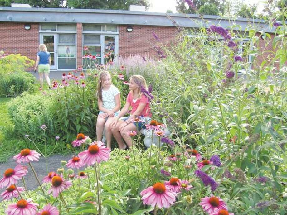 Submitted photo Guiliano DiMeo and Rachael Hird relax in the Bear Path School's SuperScience Garden after doing some weeding. The Hamden Land Conservation Trust's project Hamden's Wild Yards highlights photos of yards that attract wildlife.