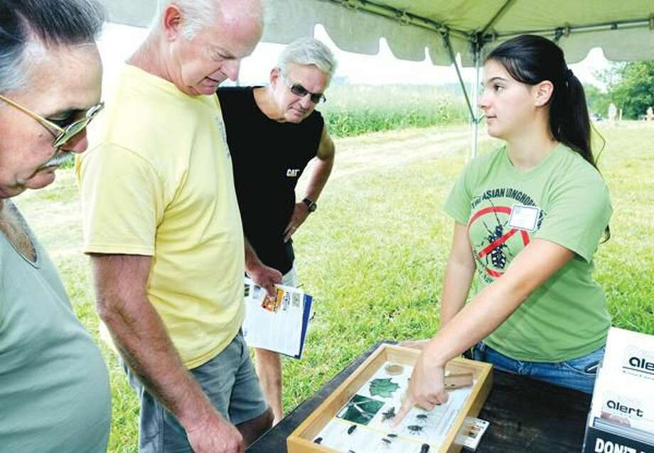 Photo by Arnold Gold Left to right, Joe Swinik, Tom Wallace and Larry Birch listen to summer research assistant Katelynn King talk about the Asian Longhorn Beetle at the Connecticut Agricultural Experiment Station's Lockwood Farm in Hamden during the 100th annual Plant Science Day last Wednesday.