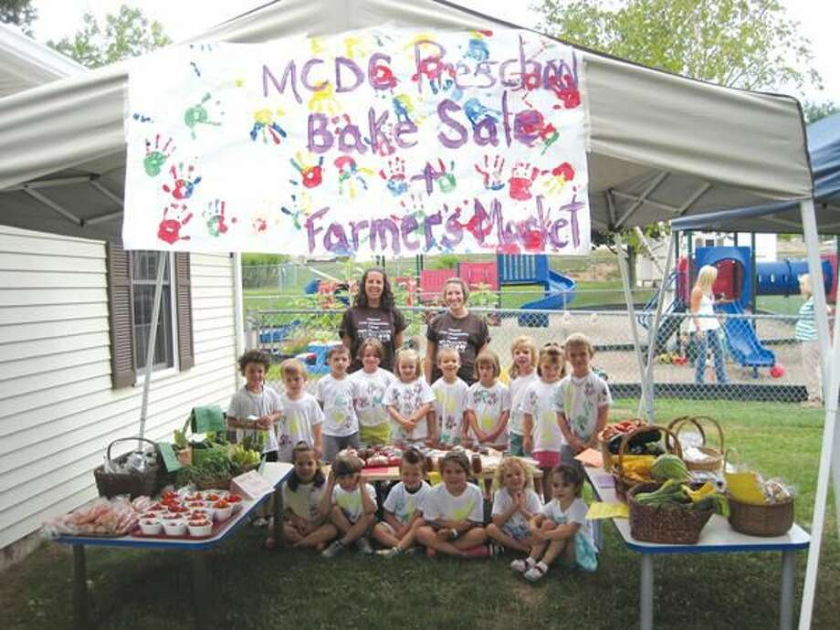 Submitted Photo Students in the pre-K class at the Masonic Child Development Center, along with teachers Christine Schardan (left) and Nicole Browell, display the fruits of their labor at the Center's Eighth Annual Farmers' Market.