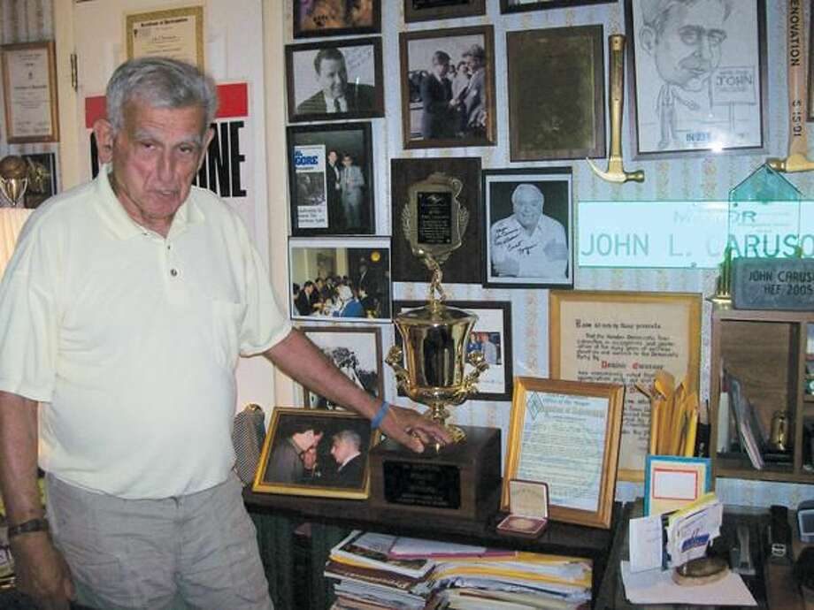 """Photo by Lynn Fredricksen Former Mayor John Carusone enjoys showing off his memorabilia he keeps in a room he calls """"The Museum"""" in the home he shares with his wife, Sylvia."""