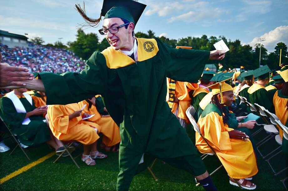 As his row is called to the state to receive their diplomas, Timothy Lettiero reaches out to a staff member to shake hands at Hamden High School commencement exercises.