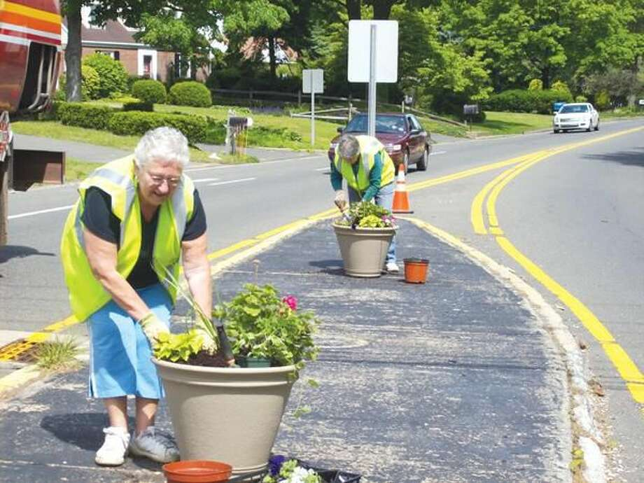 Submitted photo by Gerri Giordano Marie Tiberio and Annette Bailey fill containers at the Maple Avenue traffic island.