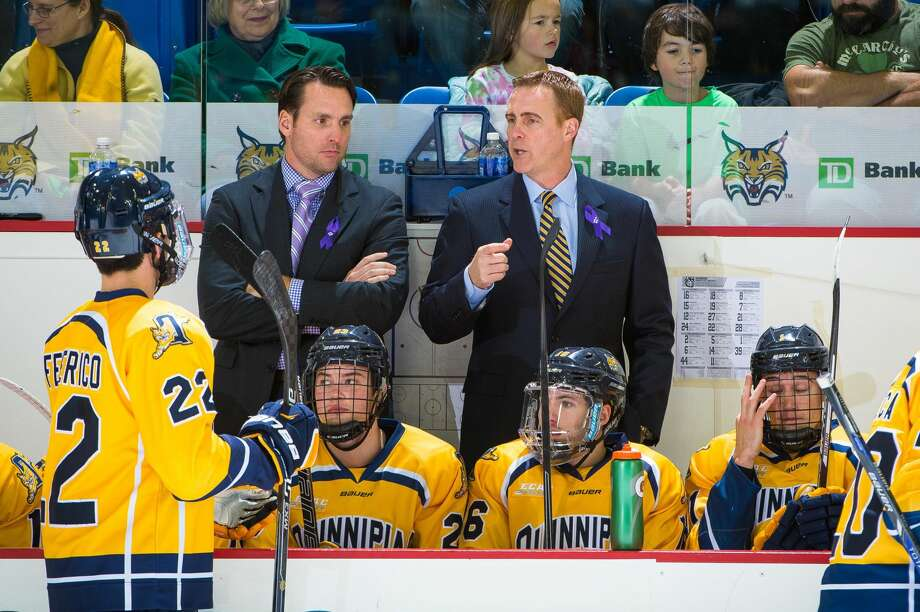 Former Quinnipiac All-American and assistant coach Reid Cashman, left, speaks with head coach Rand Pecknold behind the bench. Cashman was hired to first NHL job, as an assistant for the defending Stanley Cup champion Washington Capitals.