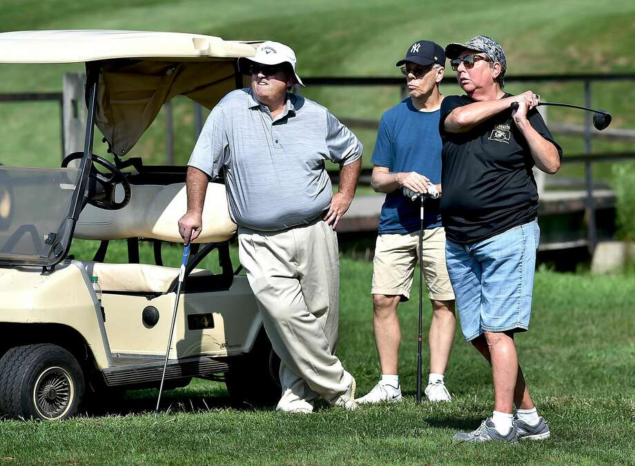 Coach Allen Misinonile, at left, watches Earla Lanier drive at the adaptive golf program sponsored by Gaylord Hospital's Sports Association Programs at Sleeping Giant Golf Course in Hamden.