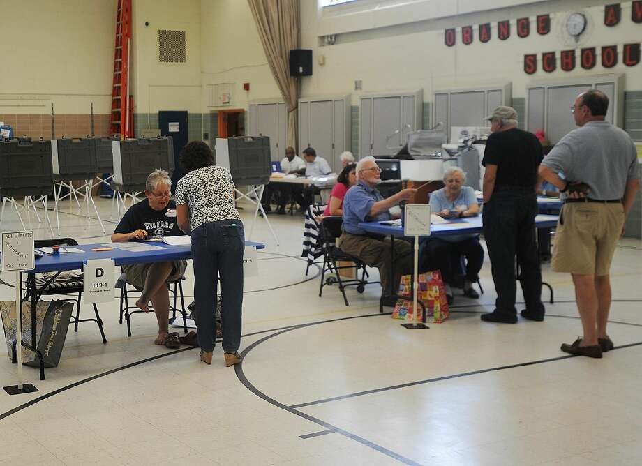 Voters check in at the polls for the Democratic and Republican primaries at Orange Avenue School in Milford on Tuesday, Aug. 14, 2018.