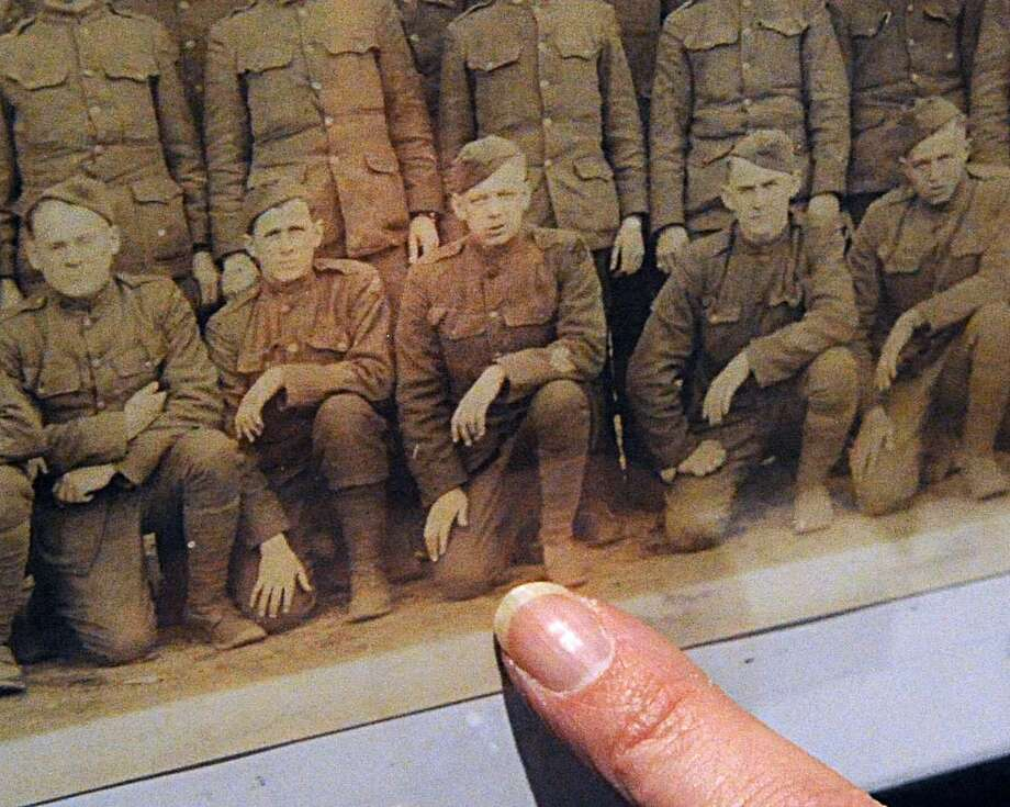 """A woman points to a WWI-era photograph of her grandfather, who served in the U.S. Army. Monday night, the Cromwell Historical Society will hold a reception to mark the opening of its summer exhibit, """"Cromwell & The Great War."""""""