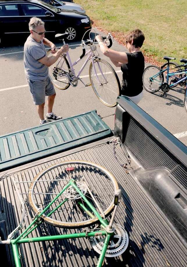 Photo by Peter Hvizdak Jerry, left, and Pat Roy of Hamden, unload one of three bicycles for the Connecticut Bike Project collection at Mt. Carmel Parish in Hamden.