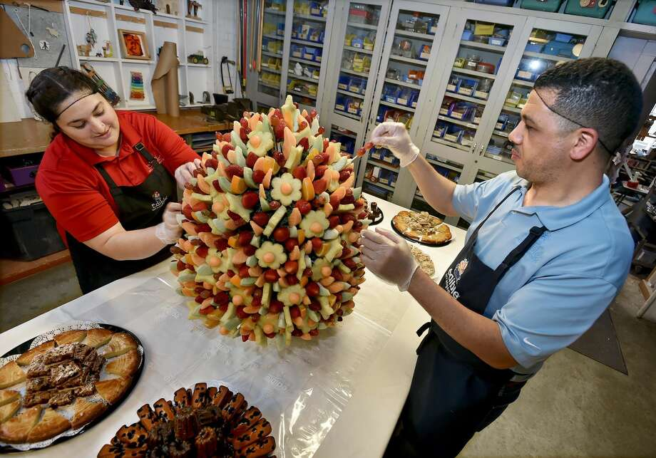 Fouad Elgoute, owner of Hamden Edible Arrangements, at right, and store manager, Saba Shanawar, put the finishing touches on a three-foot tall, 65 pound edible arrangement at the Eli Whitney Museum's 23rd annual Leonardo in Bloom Challenge fundraiser, Thursday, April 27, 2017, focusing on the beauty of flowers.