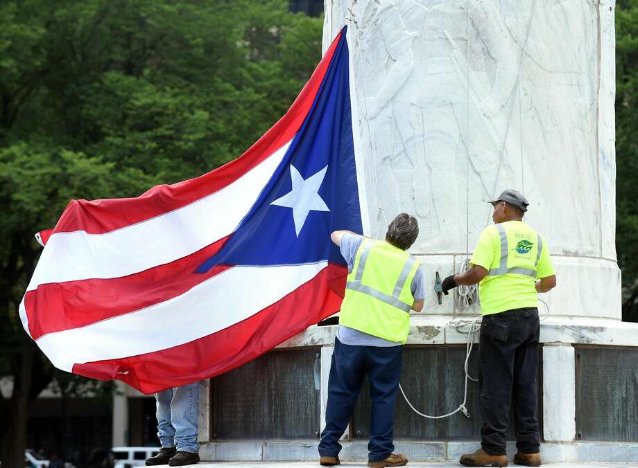 New Haven Parks, Recreation and Trees employees prepare the Puerto Rican flag to be raised on the New Haven Green in honor of the Third Annual New Haven Puerto Rican Festival. Due to inclement weather, the festival will be held indoors Saturday.