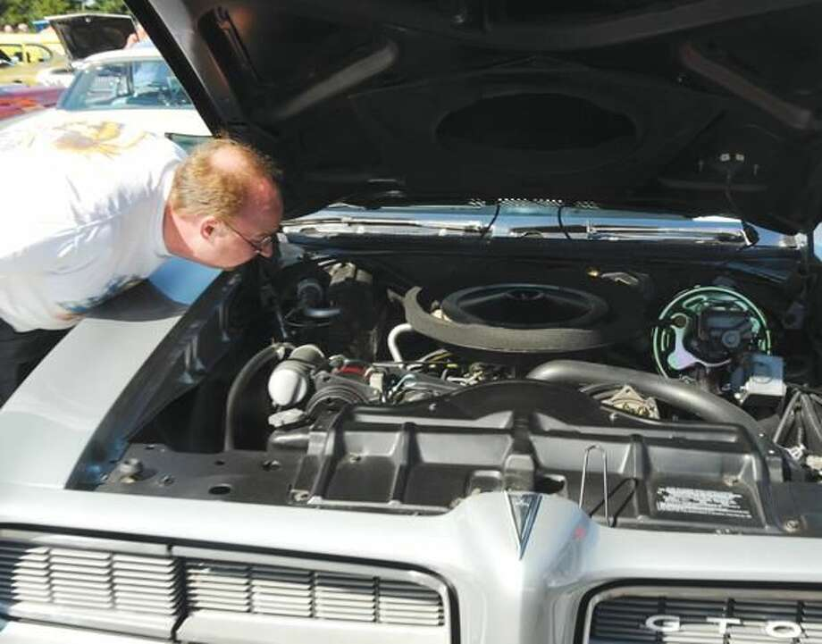 Photo by Peter Hvizdak Fred Musante looks at a 1968 Pontiac GTO during the third North Haven Police Benevolent Association's third annual benefit car show at North Haven High School.