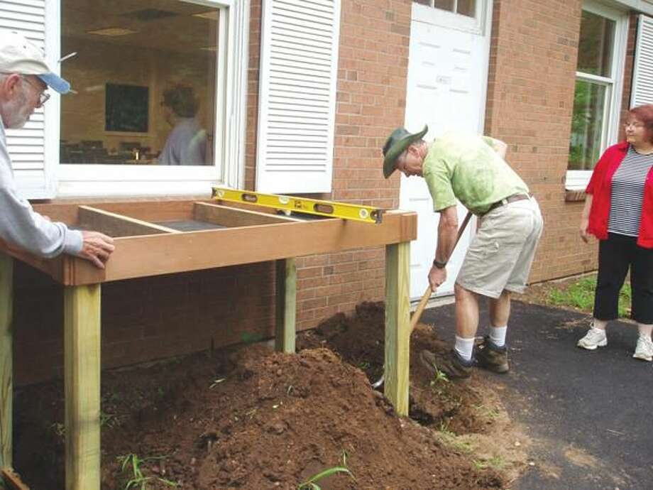 Submitted Photo Members of the Daytime Garden club recently built a herb garden table for members of the Senior Center in North Haven. Walter Brockett in the center, sets up the table; Stacey Ponzio on the right; and Mr. Nado on the left supports the table.