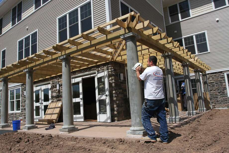Joese Oliveira, a painter with Barberi Painting (out of Waterbury), preps an exterior column at the new Pond Ridge Senior Complex of Masonicare.