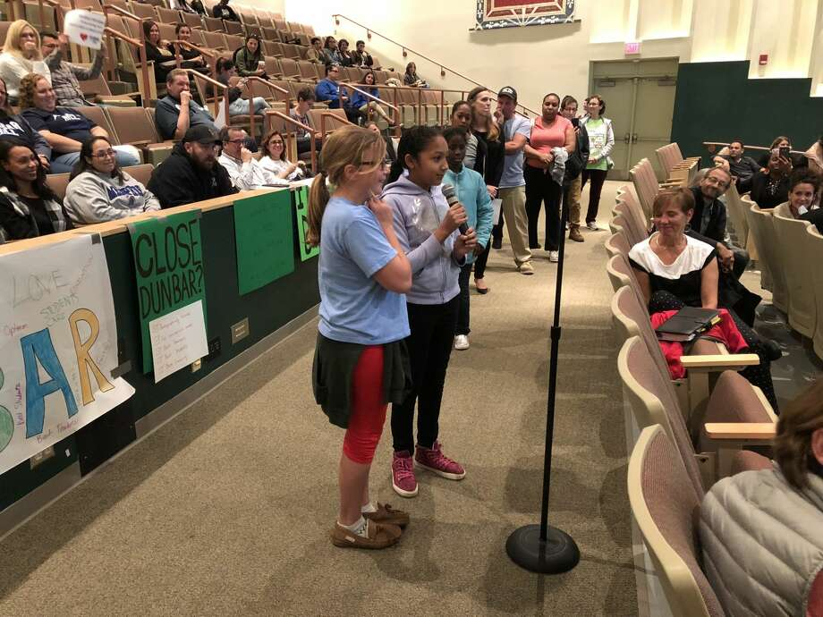 Hamden residents considered three new scenarios for the expected redistricting of the town schools Monday, Sept. 24. Here, Dunbar Hill sixth-graders Adrianna Edwards and Keanna Sammy, holding the microphone, speak.