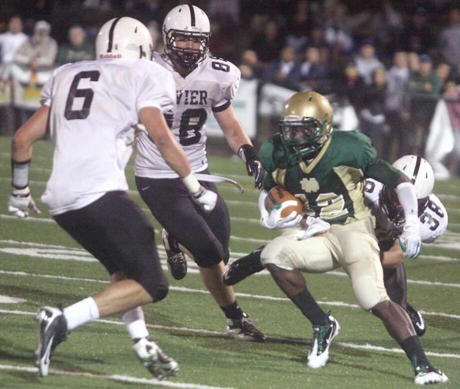 Photo by Russ McCreven The Xavier defense swarms Notre Dame-West Haven's Tirrell Young-Williams in the Falcons' 22-15 victory last Friday night.