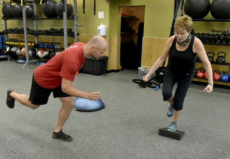 Kevin Gregory, a personal strength and conditioning trainer at Edge Fitness of Hamden, left, works with client Kathleen Bonvicini, CEO of the New Haven-based non-profit Institute for Healthcare Communication, as she physically prepares to climb Tanzania'a 19,000 foot high Mount Kilimanjaro in September to raise money for a school in Moshi, Tanzania, where she volunteers teaching.