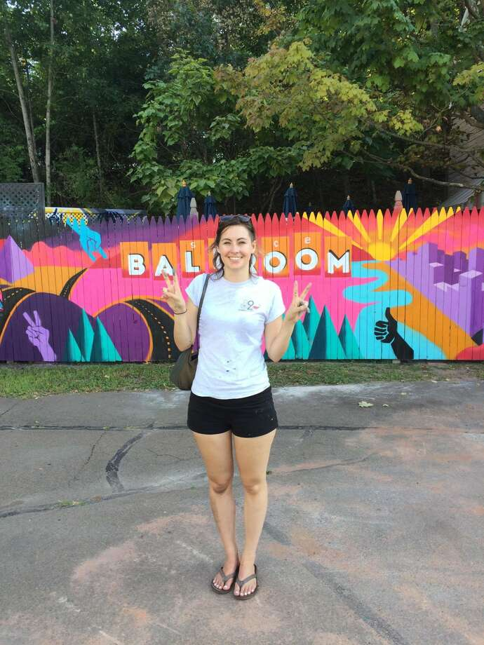 Steph Burr, a Torrington artist and graphic designer, was one of three artists in COnnecticut awarded by Two Roads Brewery for her mural work. She is pictured with a mural she recently painted for The Space Ballroom in Hamden. Burr will work with the brewery in Stratford on more projects.