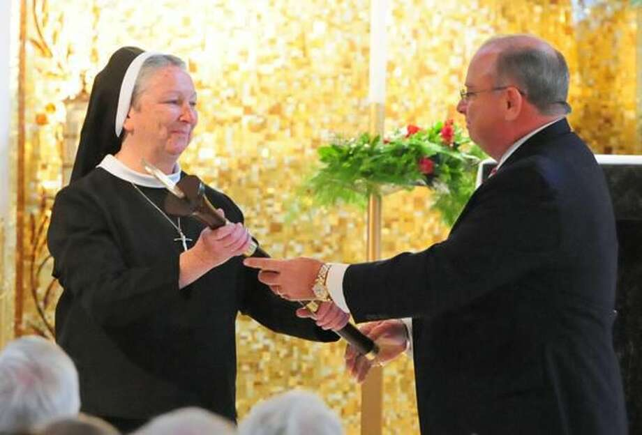 Photo by Brad Horrigan Sister Sheila O'Neill is presented with a ceremonial mace by Sacred Heart Academy Advisory Board President Eugene Harris at O'Neill's induction ceremony Sunday. O'Neill is the first president of Sacred Heart Academy.
