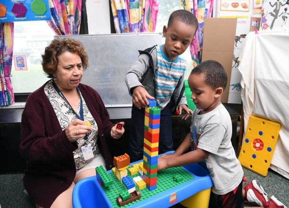 From left, Sleeping Giant Day Care Assistant Director Sharon Fuoco builds a Lego tower with Zephaniah Thomas, 4, and Avion Bowman, 4.