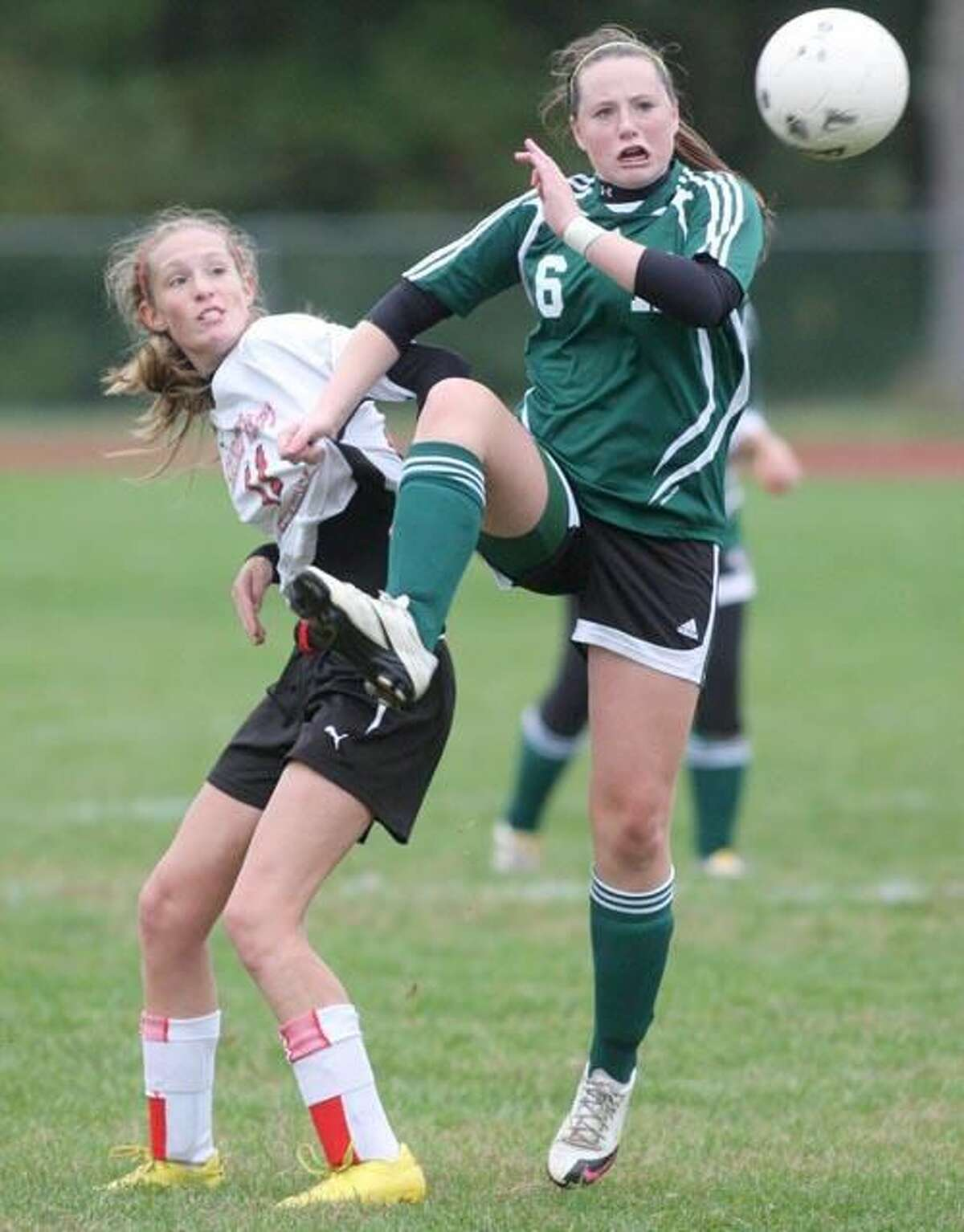 Photo by Russ McCreven Hamden's Emma Gigantino kicks the ball away while battling with Sacred Heart's Libby Carlson in the Green Dragons' 2-0 victory last week.