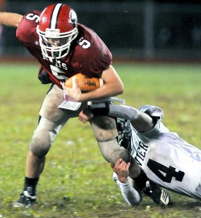 Photo by Arnold Gold/ Register Cheshire quarterback Max Slade (left) is tackled by Xavier's Ryan Jacobucci.