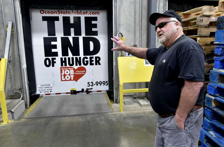 Mike Desmarais, a truck driver for Ocean State Job Lot, shows off the anti-hunger campaign slogan paint job on the back of his semi-tractor trailer truck Wednesday after he just delivered food packaged in bulk to the Connecticut Food Bank warehouse in Wallingford.