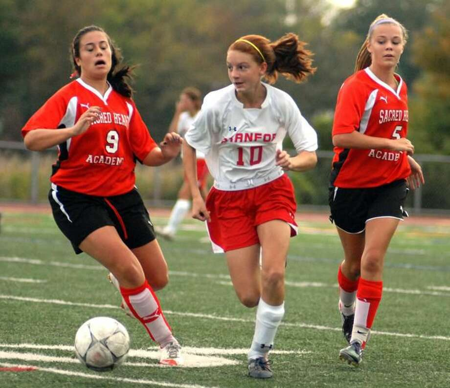 Photo by Dave Phillips Branford freshman Tanya Altrui (10) makes her move up the middle as Sacred Heart defenders Sydney Sullivan (9) and Ally Jefferson (5) close in.