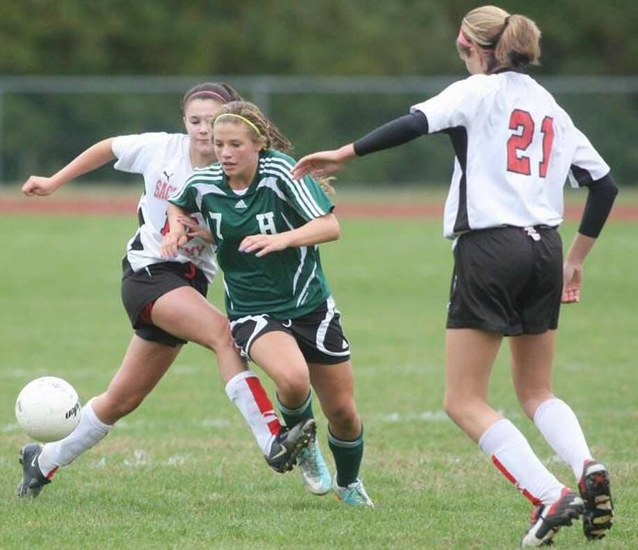 Photo by Russ McCreven Hamden's Rachel Ugolik (7) battles Sacred Heart's Danielle McPherson for control of the ball in the Green Dragons' 2-0 victory Monday afternoon at Sacred Heart.