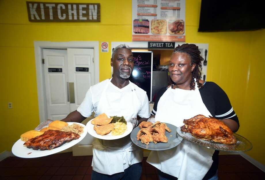 Darryl Pervis (left) and his wife, Thomea Oliver Pervis, show off some of the selections available at their store, DPERV'S T.O.P. BBQ on Dixwell Ave. in Hamden. Darryl is holding a plate of baby back ribs, chopped pork bbq and cornbread (left) and another with fried swai fish, macaroni and cheese and collard greens. Thomea is holding a plate of fried chicken wings and another with a whole rotisserie bbq chicken.