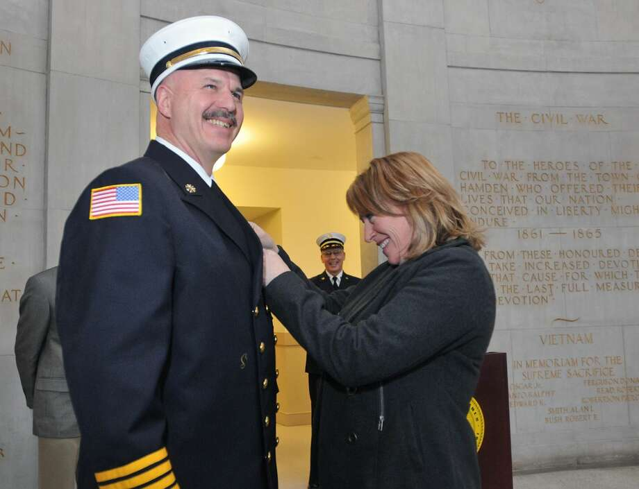 Hamden Deputy Fire Chief Gary Merwede gets his badge pinned on by his wife, Cheryl, during a swearing-in ceremony at town hall.