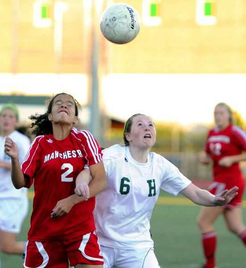 Photo by Peter Hvizdak/ Register Manchester's Jasmyn Spann, left, and Hamden's Emma Gigantino battle for position for a header in the Dragons' 3-1 victory last week.