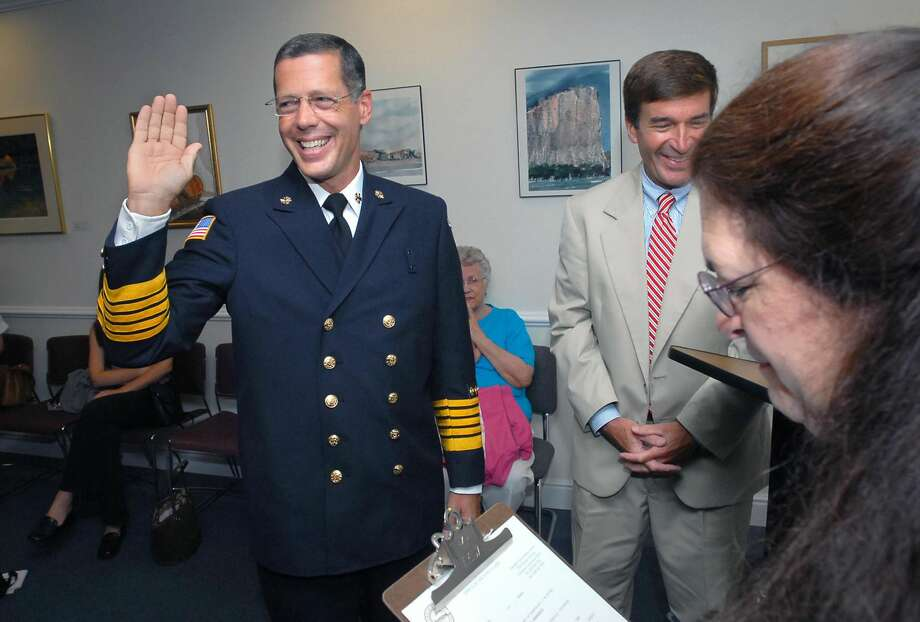 David Berardesca is sworn in as the new Hamden Fire Chief by town clerk Vera Morrison at the Hamden Government Center on 8/15/2006. At right in back is Hamden Mayor Craig Henrici.